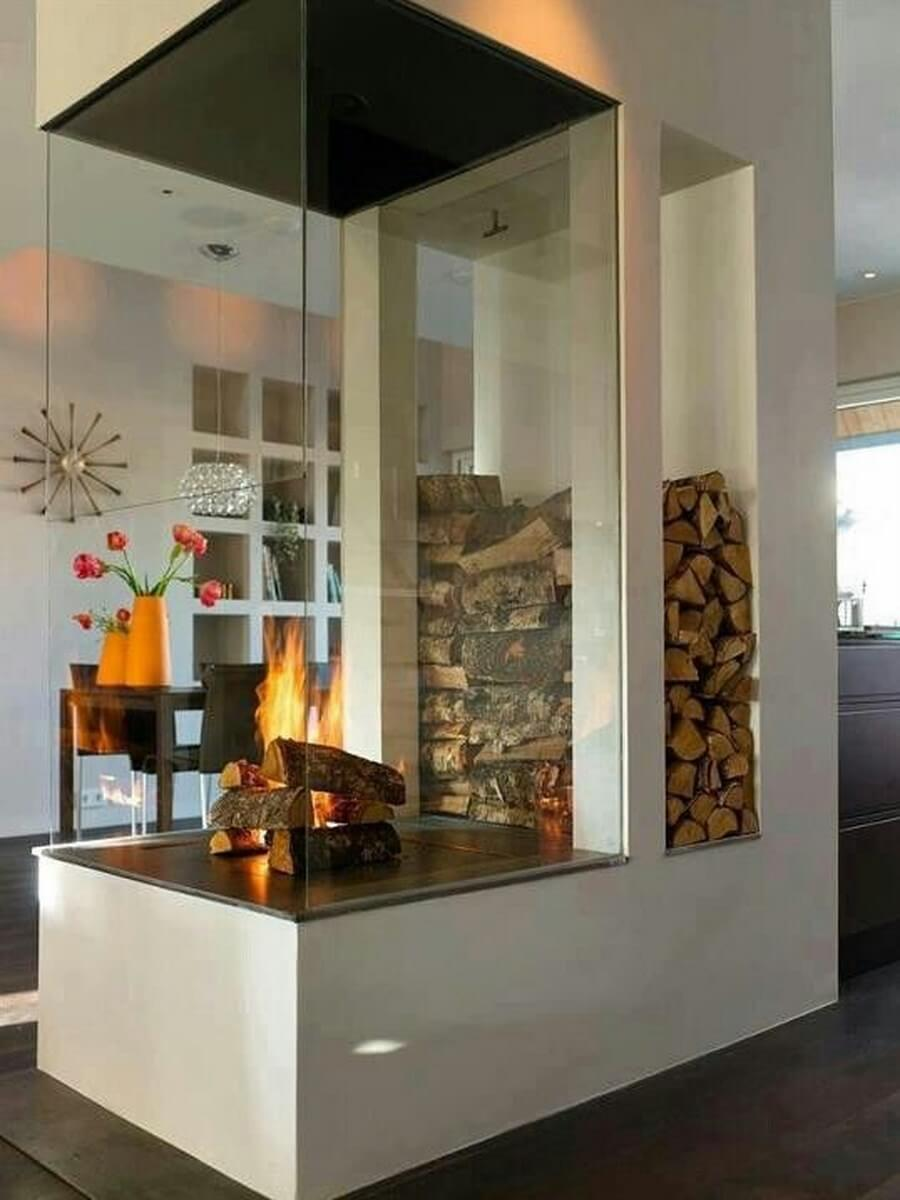 Massive glass fireplace with firewood pile