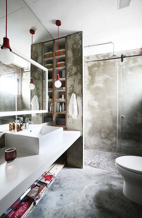 Concrete industrial bathroom with red light fixtures