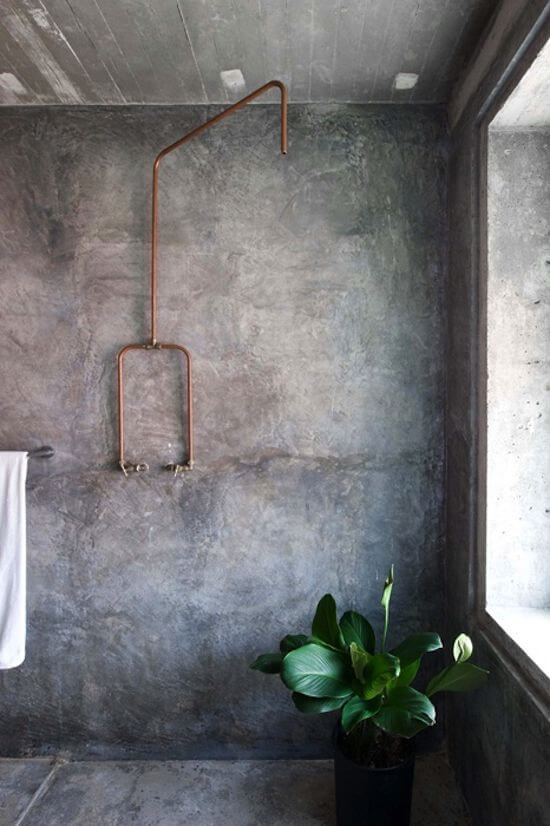 Super spacious concrete bathroom with houseplant