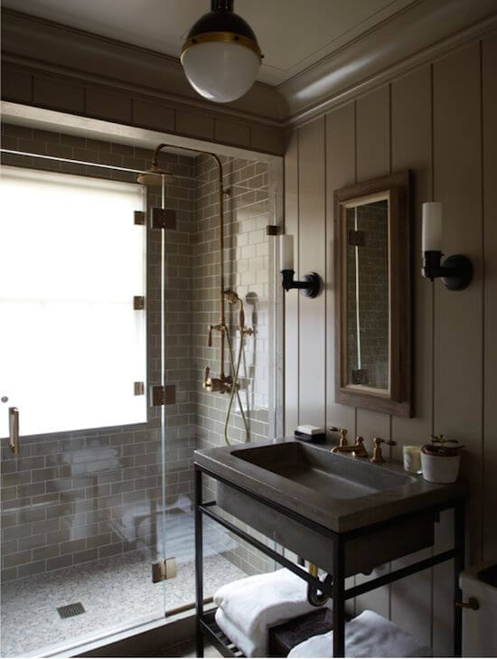Striking industrial bathroom with tiled shower and exposed metal pipes