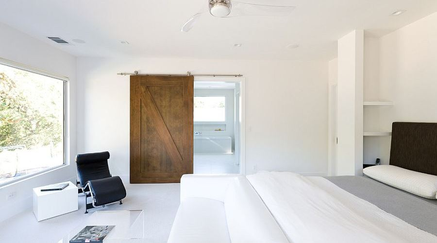 All white minimal bedroom with barn door for the bathroom