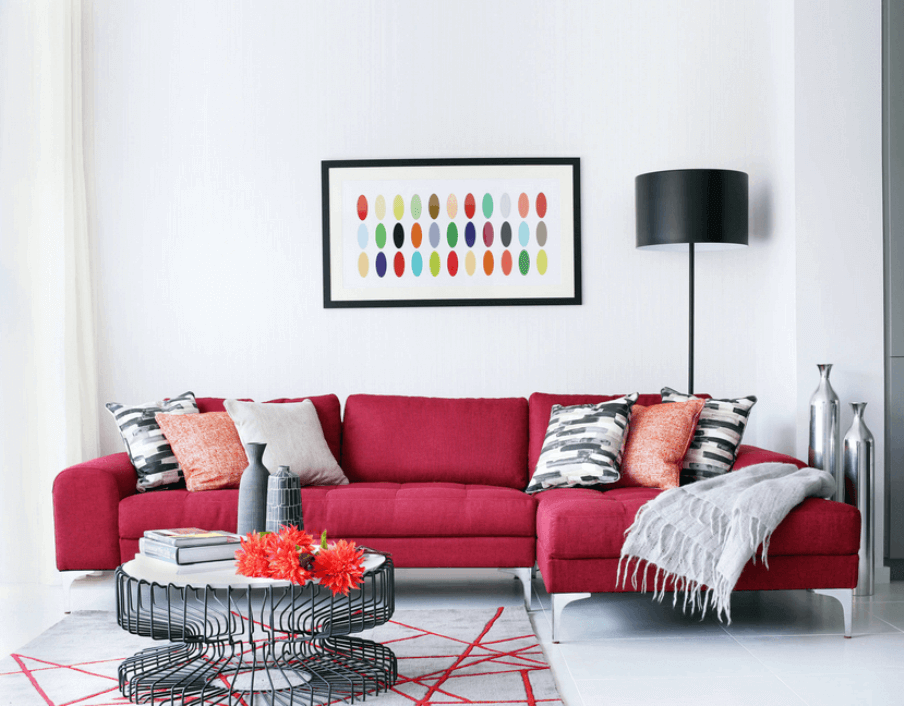 Red couch in a bright white living room