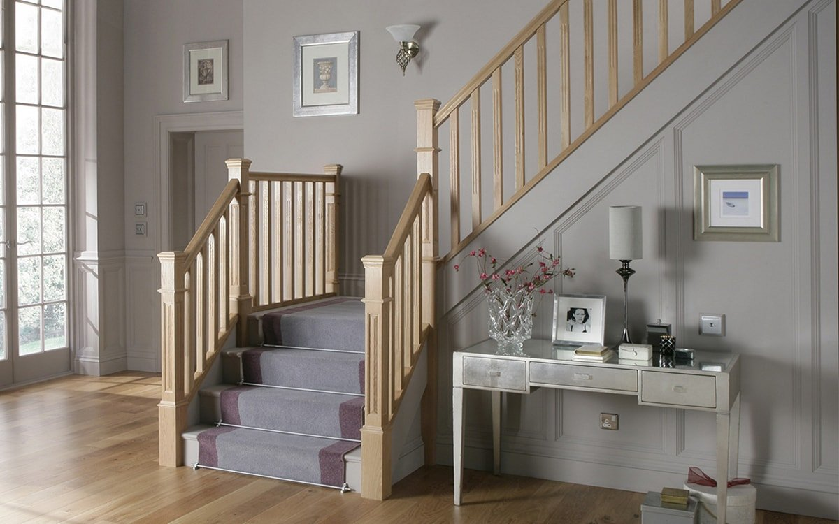 Staircase with wooden railing and carpet steps