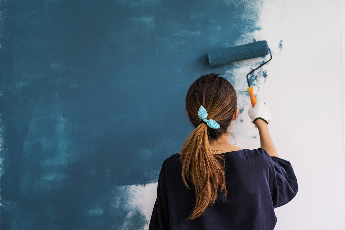 Woman painting the wall blue