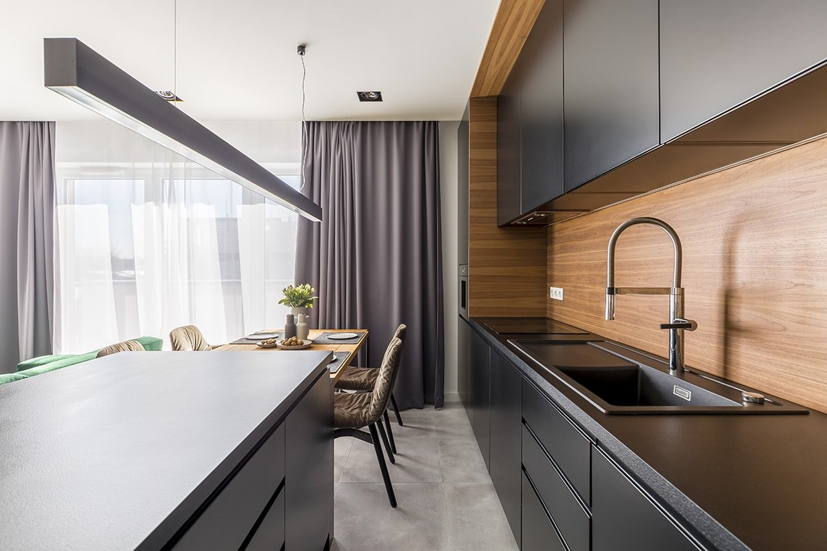 Kitchen with black cabinets and wood paneling