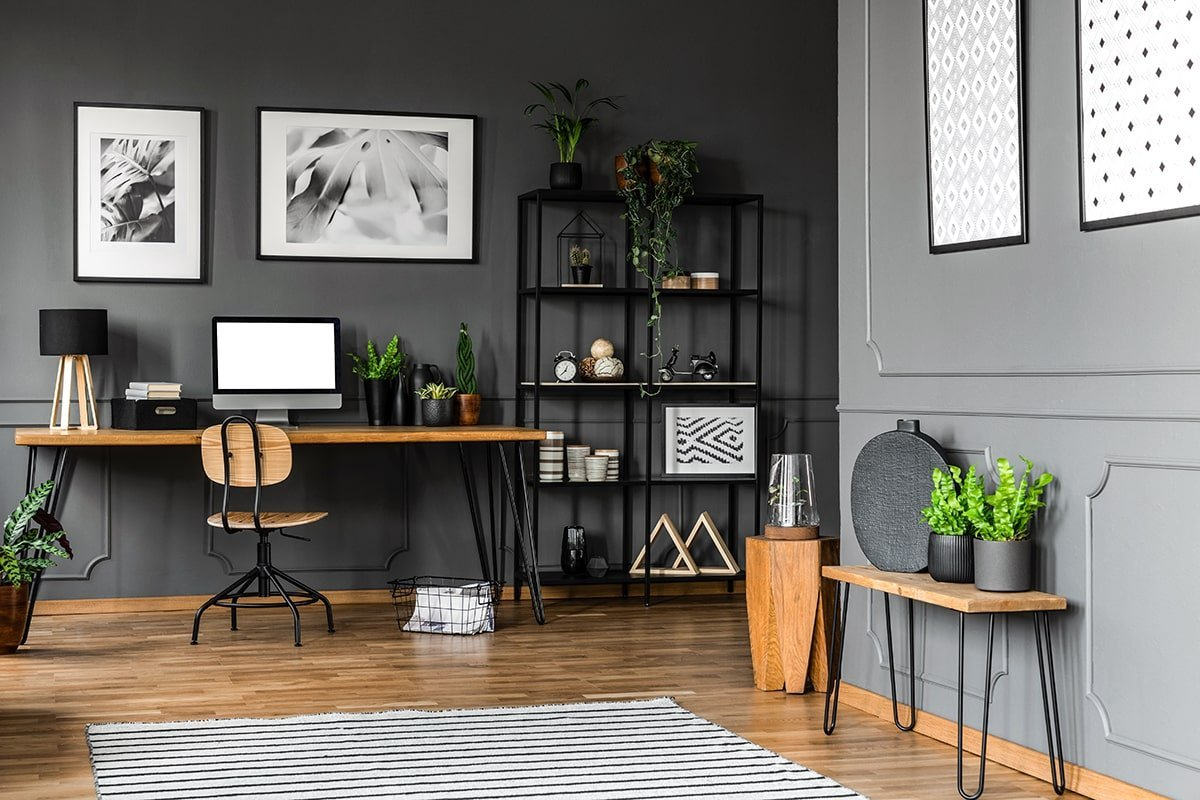 Home office with wood furniture and dark walls